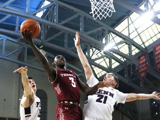 Junior guard Shizz Alston Jr. (center) attempts a layup over Penn sophomore forward AJ Brodeur (left) and sophomore guard Ryan Betley during the Owls' 60-51 win against the Quakers on Saturday at The Palestra. | EVAN EASTERLING / THE TEMPLE NEWS