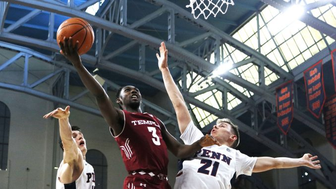 Junior guard Shizz Alston Jr. (center) attempts a layup over Penn sophomore forward AJ Brodeur (left) and sophomore guard Ryan Betley during the Owls' 60-51 win against the Quakers on Saturday at The Palestra.   EVAN EASTERLING / THE TEMPLE NEWS