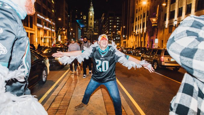 An Eagles fan celebrates on the median of Broad Street, flapping his arms like wings, after the Eagles won the NFC Championship to advance to the Super Bowl on Sunday. | SYDNEY SCHAEFER / THE TEMPLE NEWS