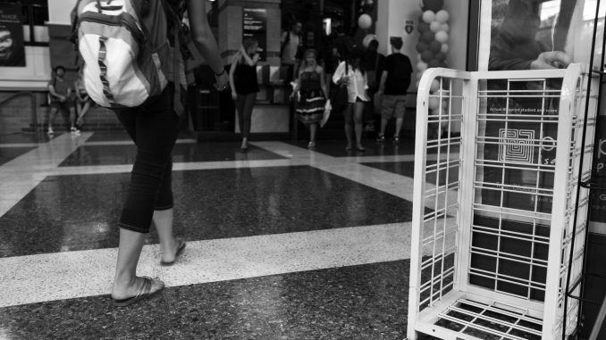 Students walk by an empty bin previously reserved for the New York Times. Residential Life and Student Activities canceled the readership program. ( KATE MCCANN / TTN )