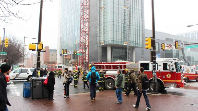 Bystanders look on as firefighters contain a fire on the 18th floor of Morgan Hall. The $216 million, 27-story residence hall apparently received little damage from the fire. | ANGELO FICHERA / TTN