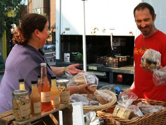 Shannon Brown (left) of Green Aisle Grocery discusses bread options with customer Ezekiel Zagar at Fountain Farmers' Market, which also offers other fall favorites such as tomatoes, corn and sweet potatoes. | Taylor Spicer TTN