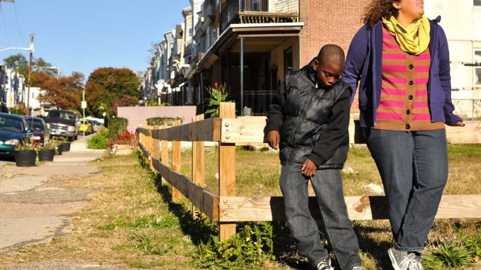 Emaleigh Doley (right) and Kevon Lewis stand in front of an empty lot on West Rockland Street that she and her sister Ainé helped improve in 2008.   JACOB COLON TTN