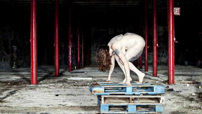 "Sarah Bloom poses for her series, ""Discarded,"" in an abandoned building.