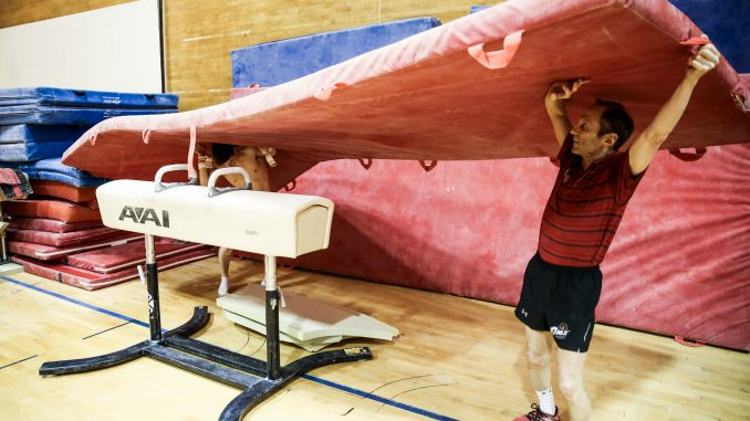 Coach Fred Turoff lifts a mat during an April practice in McGonigle Hall. The men's gymnastics team has practiced in the same location for the past 32 years. | HUA ZONG TTN