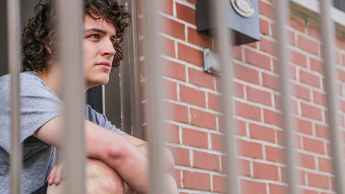 Junior film and media arts major Billy Denham sits outside his front door on the 1900 block of 18th Street. On Sunday, two armed men allegedly tied up his roommates and fled with cash and electronics. Denham said he was not home for the incident. Andrew Thayer | TTN