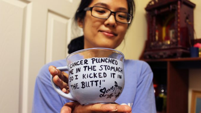 Anne Ha holds a glass cup she painted. After her diagnosis in June, Ha began decorating mugs and other items with her own inspirational quotes. Claire Sasko   TTN