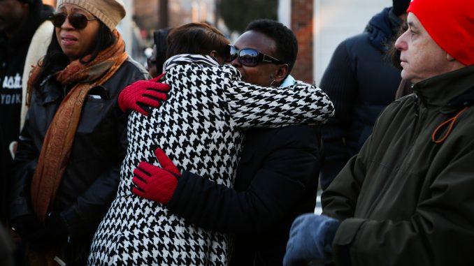 Residents gathered at the intersection of 12th and Jefferson streets on Friday to mourn Kim Jones, who was shot and killed at the corner three days earlier. | Jenny Kerrigan TTN