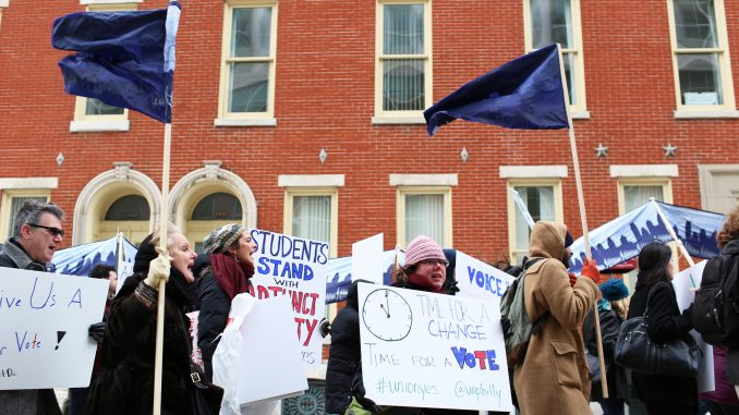 "Adjunct professors chant, ""Let us vote,"" as they march down Liacouras Walk on Feb. 23. Pending a March 19 hearing with the Pennsylvania Labor Relations Board, adjuncts are demanding a vote for or against unionization. 