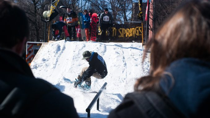 Nick Yomey rides the rail as students look on at the Bell Tower Rail Jam, organized by the Snowboarding Club, on Feb. 13. | Allan Barnes TTN