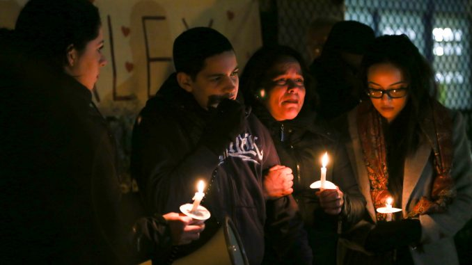 Alex Rojas-Garcia's sister Aleida Silva-Garcia (left), son Alex Jr., sister Enid Rojas and daughter Brianna hold candles at a vigil for him in Feltonville on Feb. 7. | JENNY KERRIGAN TTN