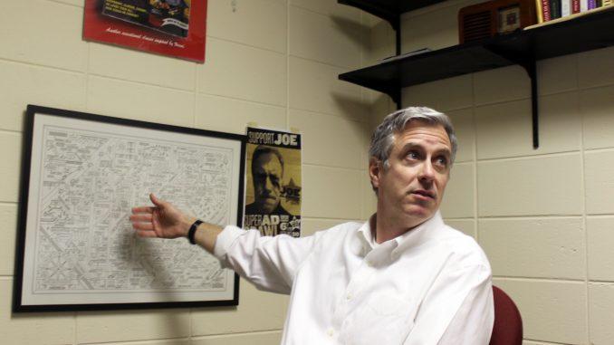 Joe Glennon, the faculty director of Diamond Edge Communications, motions to his favorite poster of Bruce Springsteen lyrics. Glennon's work has always focused on copywriting.   Grace Wilson TTN