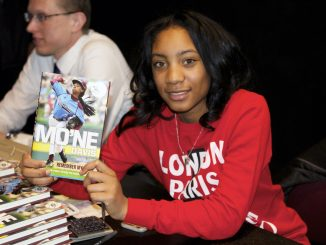 "Mo'ne Davis holds a signed copy of her book, titled ""Mo'ne Davis: Remember my Name: From First Pitch to Game Changer."" 