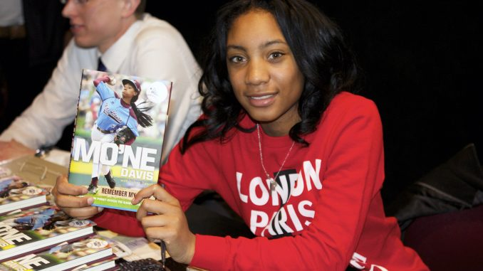 """Mo'ne Davis holds a signed copy of her book, titled """"Mo'ne Davis: Remember my Name: From First Pitch to Game Changer."""" 