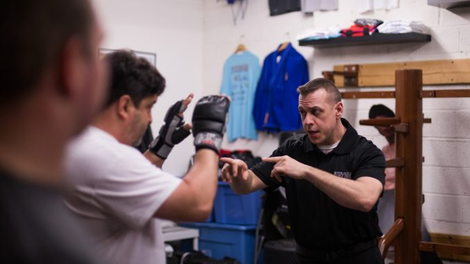 Allen Chambers, Temple alumnus and owner of Philadelphia Self Defense in Old Kensington, instructs students while they warm up before class. | Margo Reed TTN