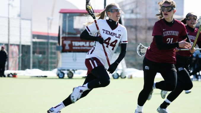 Junior midfielder Nicole Tiernan cradles the ball during the Owls' 17-7 win against Lafayette Feb. 28. Tiernan scored twice in defeat Saturday in the Owls' 14-8 loss to Vanderbilt. | Paul Klein TTN FILE PHOTO