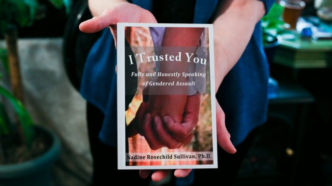 """Professor Rev. Dr. Nadine Rosechild Sullivan holds her book, """"I Trusted You"""", which discusses violence against women. 
