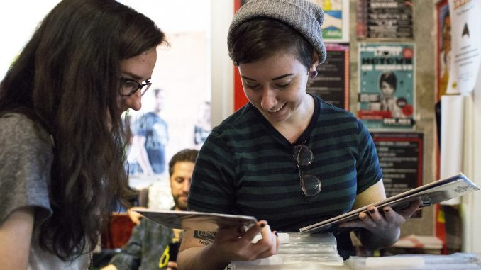 """Lauren DeLucca (left) and Rachel Dispenza, the organizers of """"Girls to the Stage,"""" a compilation and benefit show, look through albums at Creep Records on Record Store Day. 