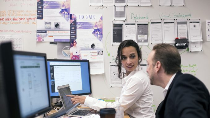 Yasmine Mustafa (left) and Anthony Gold of ROAR work on business plans to discuss at an upcoming meeting. The company hopes to launch by December. | Margo Reed TTN