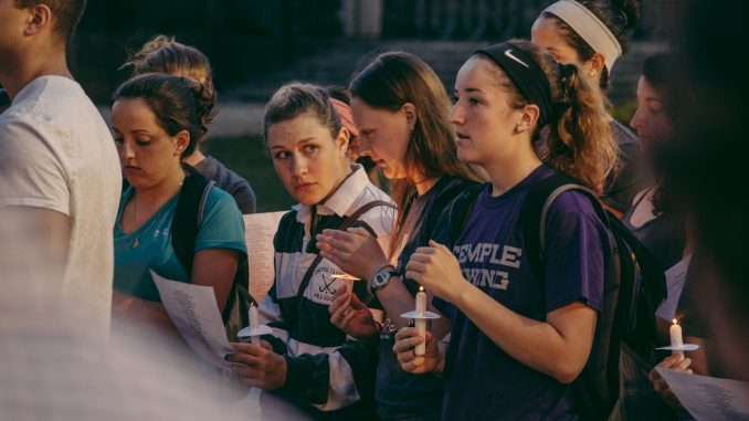 """Attendees of the vigil sang along to R. Kelly's """"The World's Greatest"""" in support of Rachel Hall and her family. Hall's lacrosse team played the song before games this spring.