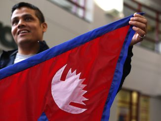 """Buddha Khatri, who is pursuing a doctorate in chemistry, holds a Nepal flag at the Student Center on Friday. Geometric instructions on reproducing a Nepali flag are part of the country's constitution, making it """"the most mathematical flag,"""" he said. 