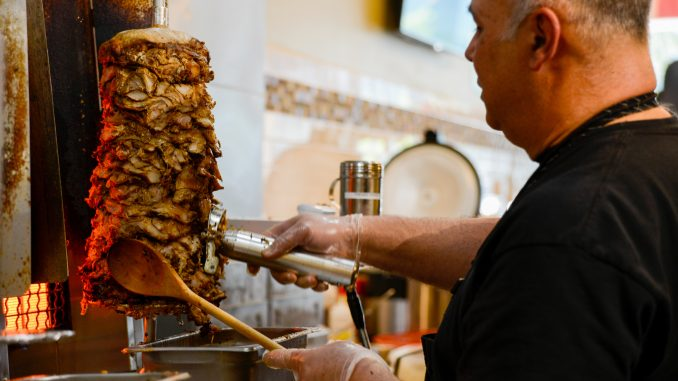 Co-owner, Omar Alsaadi, carves layers of chicken shawarma for the lunch rush. | Brianna Spause TTN