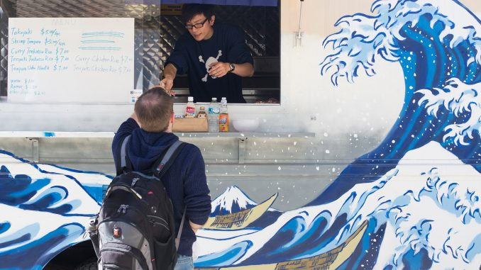 Jeff Ji, owner of the Tabeteki and Vegan Tree food trucks, serves lunch to a student. | Margo Reed TTN