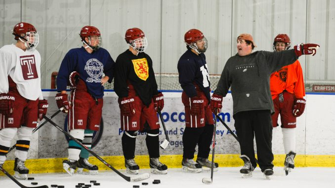 Coach Roman Bussetti (second from right) addresses the ice hockey team during a recent practice. | Brianna Spause TTN