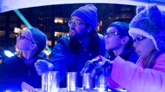 Children Mayson Ritchie (left), Taylor Trojan and Catherine Trojan work with Thomas Roland, Klip Collective art director, on the interactive light and music performance at Dilworth Park as part of the Red Bull Art of Can opening Oct. 3. | Margo Reed TTN