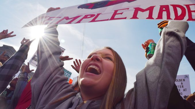 "Jordan Stewart raises her ""Temple Made"" sign at ESPN's College GameDay Oct. 31 at Independence Hall. 