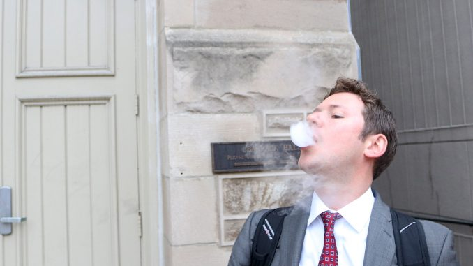 John Basenfelder, a third-year law student, is one of many Temple students who have taken up vaping. Vaping is the common term for using an e-cigarette or vaporizer that heats liquid, which contains nicotine, to produce vapor the user inhales. The practice has been adopted by many former smokers as a healthier alternative to smoking, but some are still skeptical about its benefits.   Evan Easterling TTN