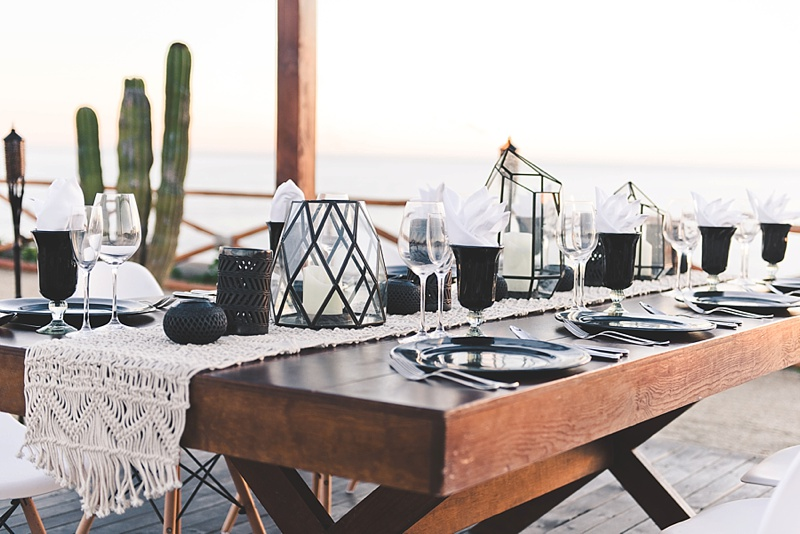 Geometric and modern wedding table decor ideas with glass black vases and black clay candle holders and macrame table runner