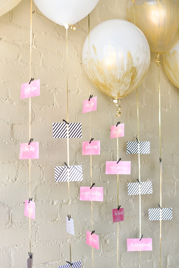 Hanging wedding escort cards on balloons