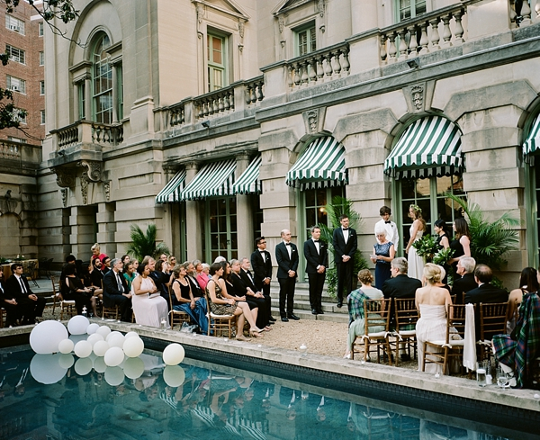 Poolside wedding ceremony with white balloons in the water for decor