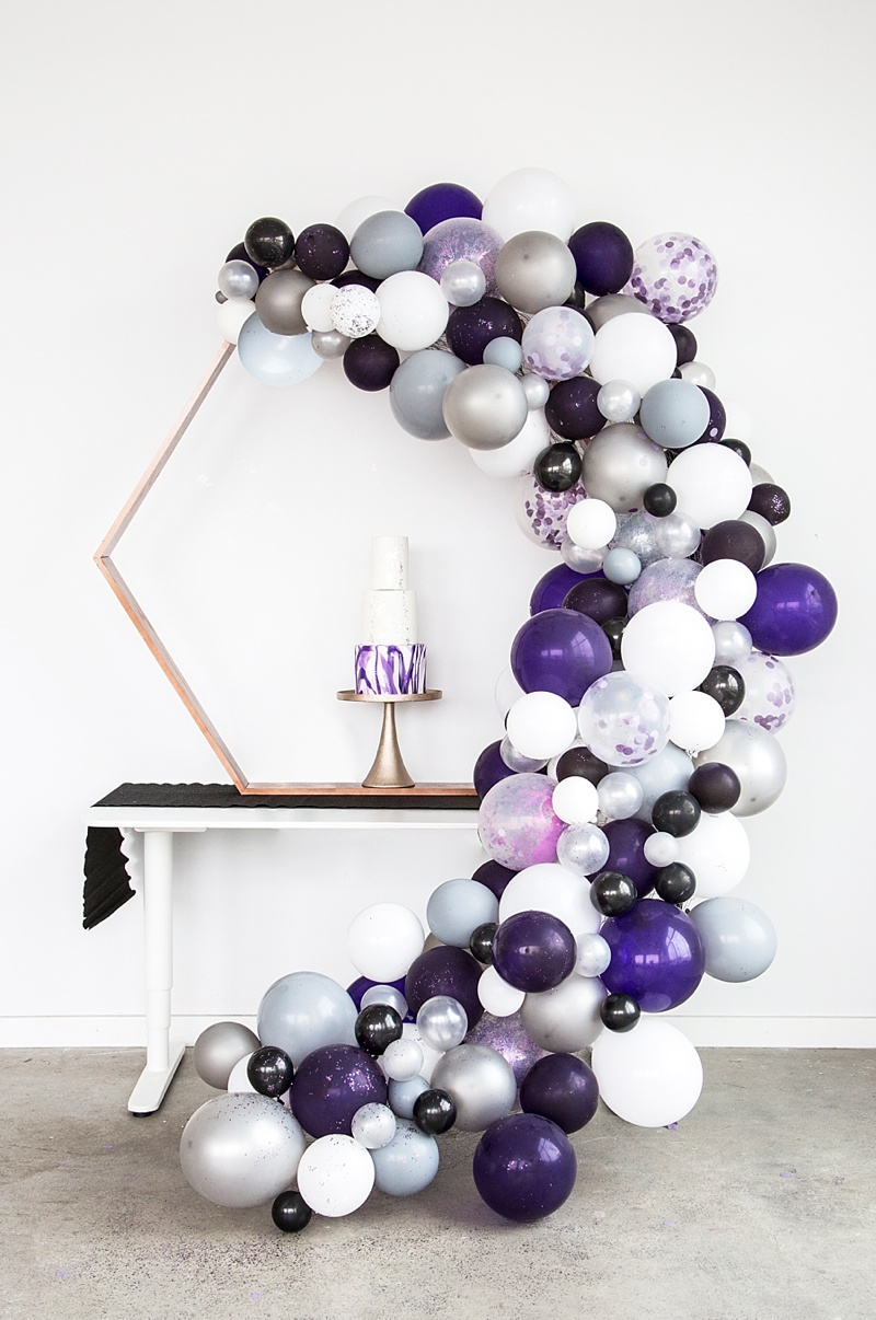 Purple balloon arch for unique wedding cake display