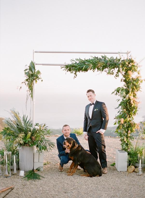 Industrial modern beach wedding arch with asymmetrical greenery