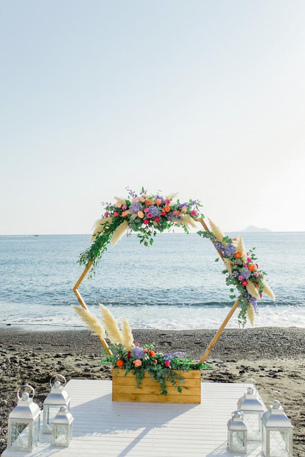Hexagon beach ceremony arch with florals and pampas grass