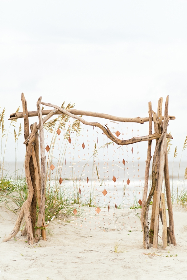 Driftwood beach wedding ceremony arch with geometric garlands