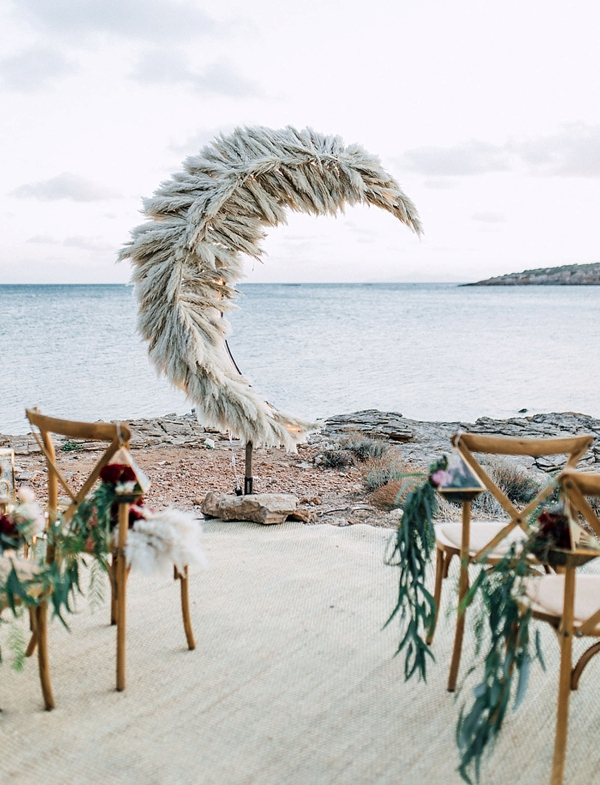 Crescent moon shaped beach wedding ceremony altar made of pampas grass