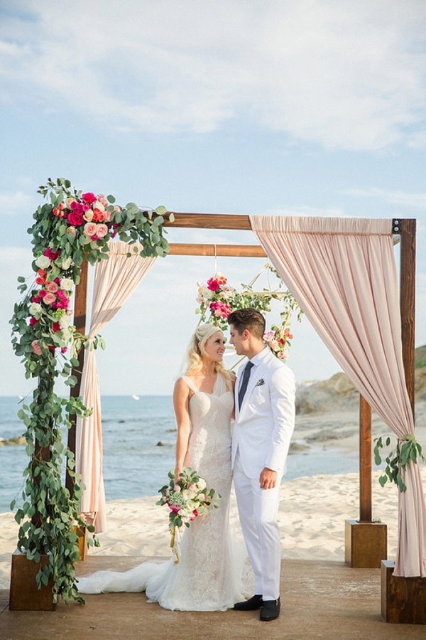 Asymmetrical wedding floral decor on elegant chuppah