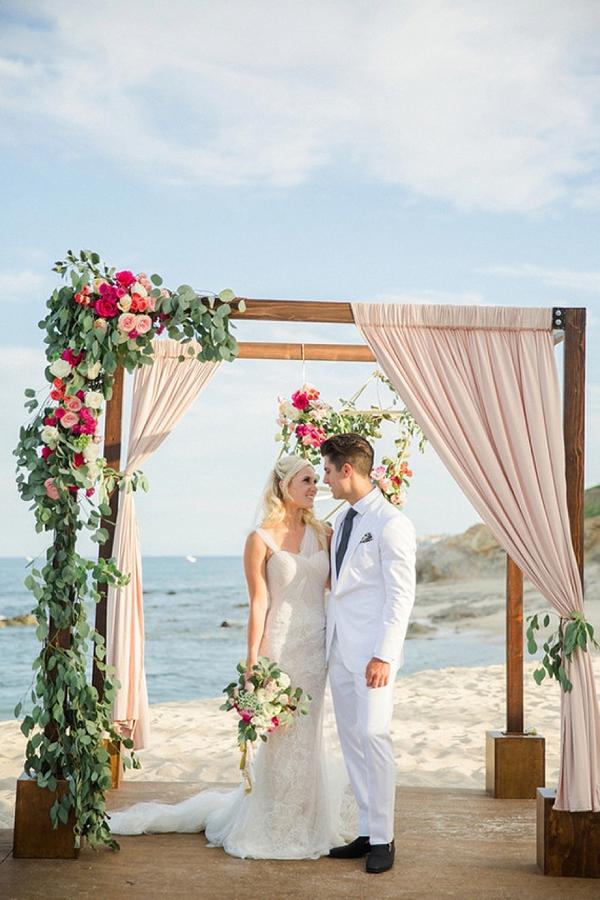 Asymmetrical wedding floral decor on elegant chuppah