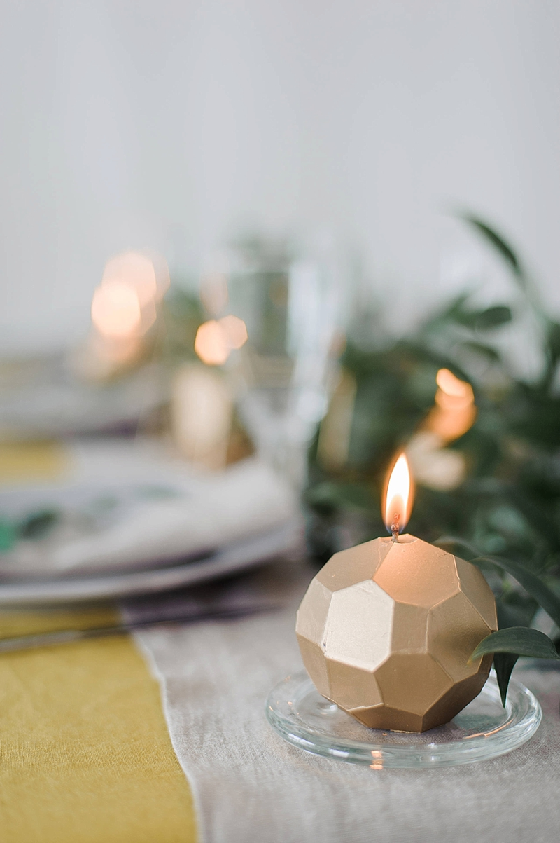 Geometric and faceted gold candle perfect for a modern winter holiday wedding