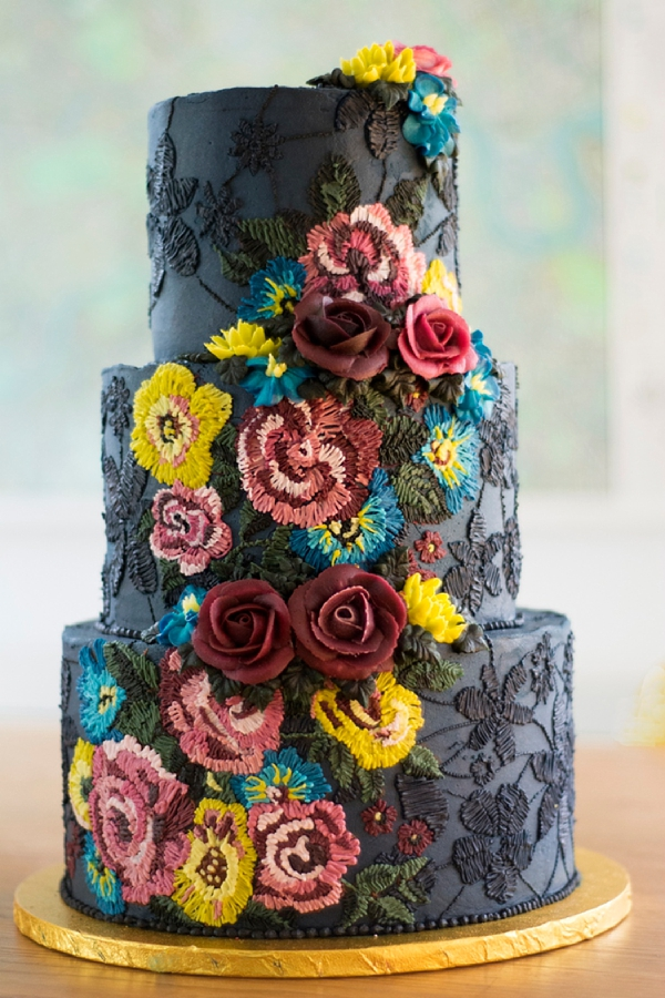 Embroidery inspired black wedding cake with colorful details