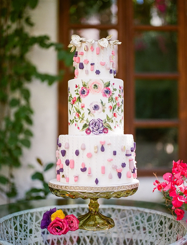 Fun and playful tiered white wedding cake with hanging sugar beads and painted florals