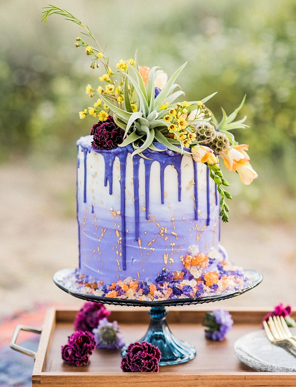 Purple and white drip wedding cake with rock candy texture and gold flecks