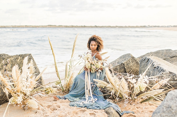 Gorgeous natural hair beach bride surrounded by organically arranged pampas grass