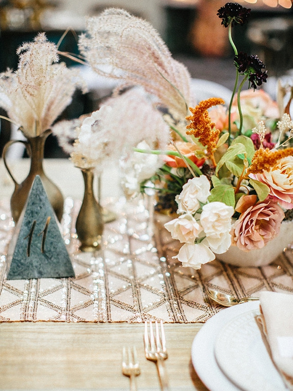 Wispy pampas grass wedding centerpiece with eclectic decor and sparkly table runner