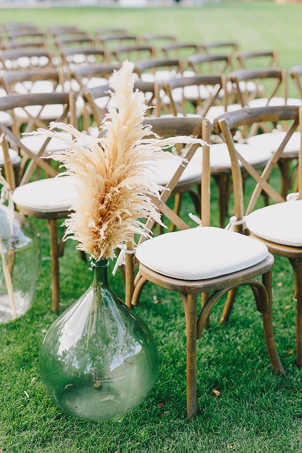 Simple pampas grass in green glass vases for wedding ceremony aisle decoration