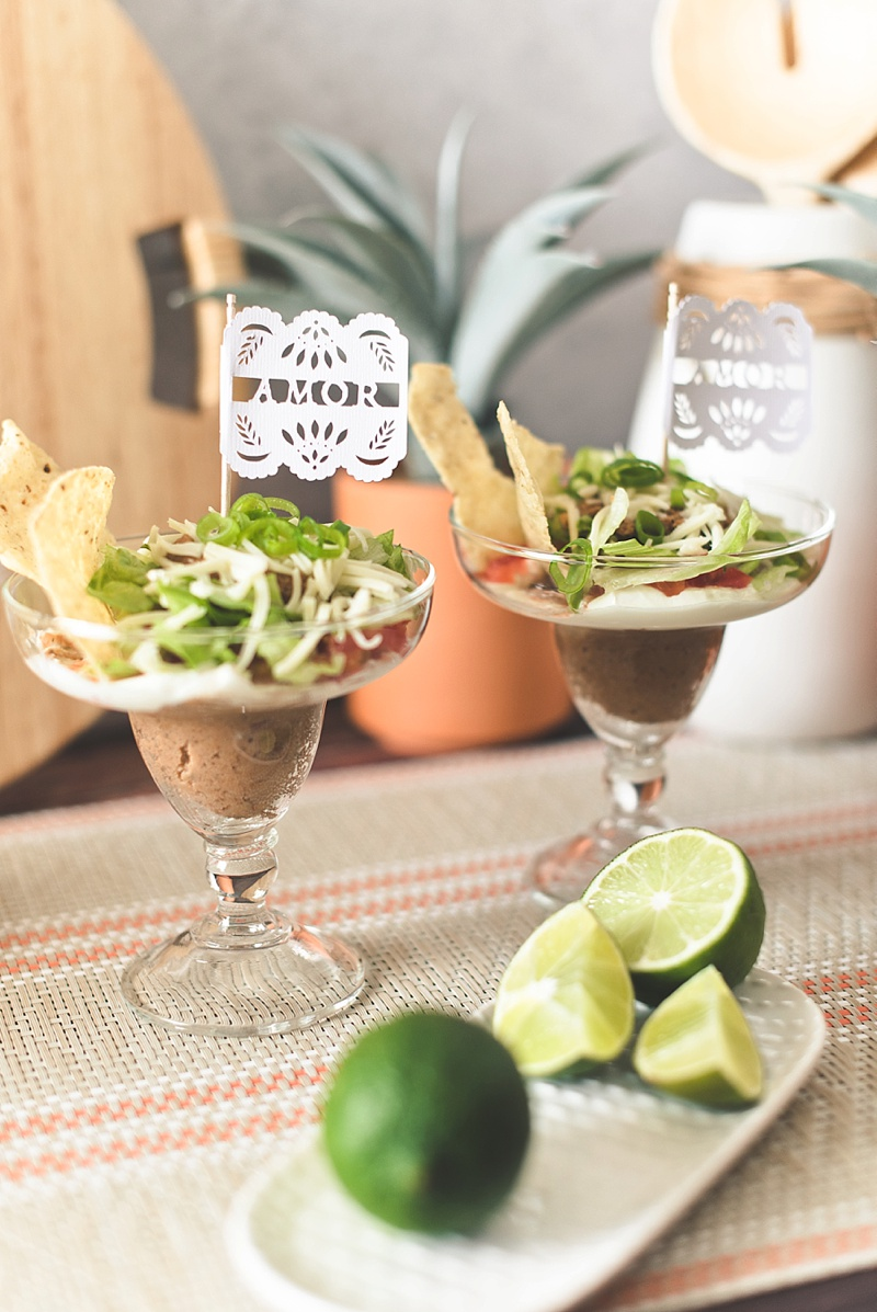Layered taco bean dip recipe for fiesta wedding or bridal shower with cute DIY papel picado food pick flags