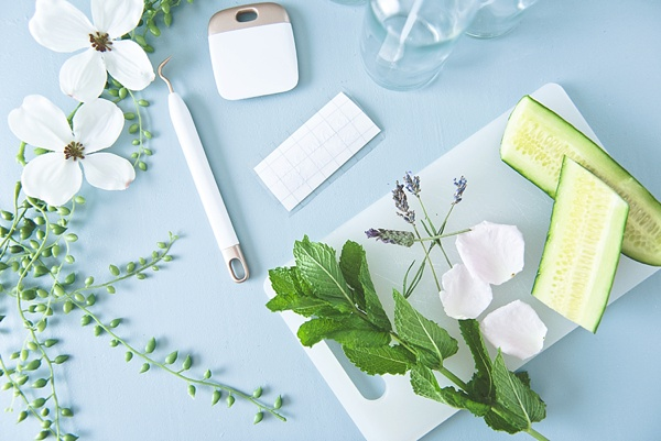 Materials for a chic DIY misting bottle with herbs and flowers